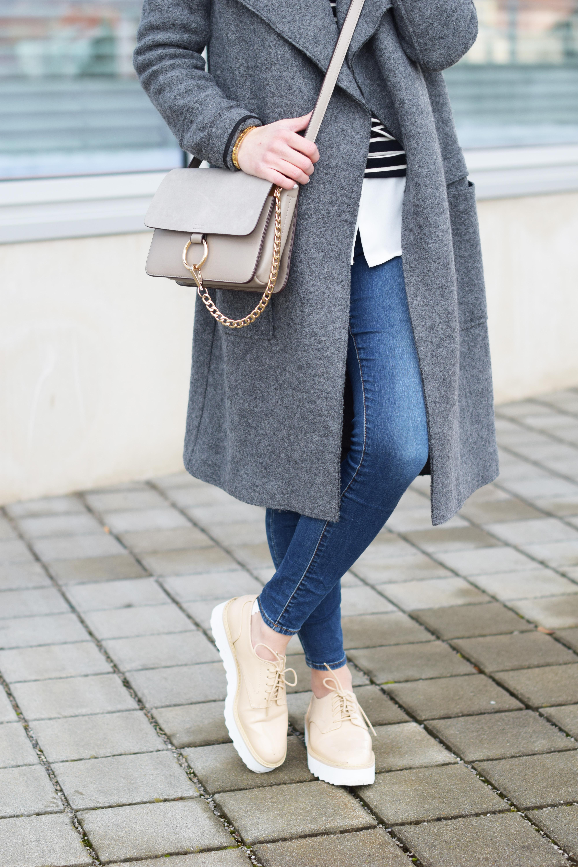 Langer grauer Mantel von Zara mit Streifenshirt, weißer Bluse und Plateau Schuhen