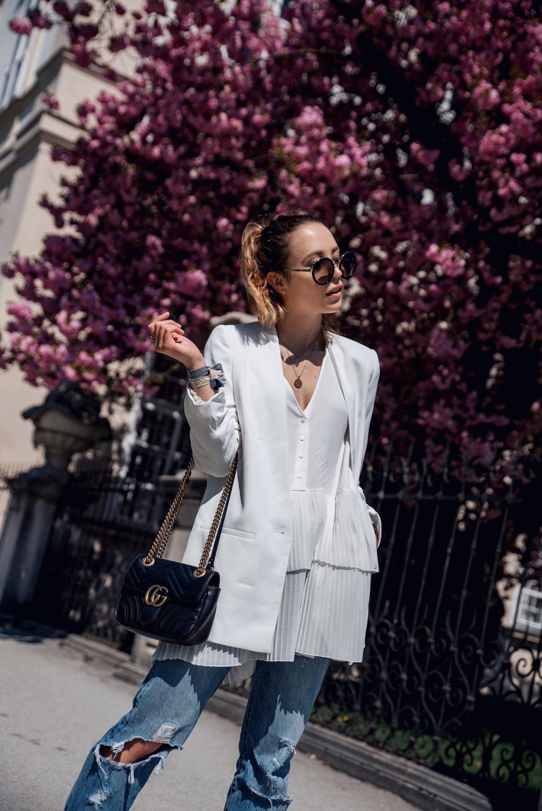 Casually Chic: Outfit mit weißem Blazer, plissierter Bluse und Boyfriend Jeans